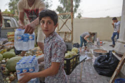 A displaced Iraqi helps unload water in Community Center's Kitchen at the Church of St. John the Baptist. Photo courtesy of Alexander Buehler for Caritas Iraq